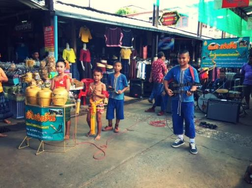 Children play in a band in the local outdoor market.